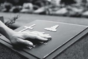 Niswanger Law in Monroe, La answers the common question: What is Probate?; black and white image of woman's hand resting on gravestone at cemetery