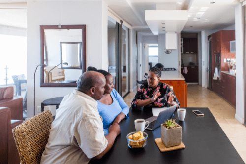The Merits Of Estate Planning For Adults Of Every Age with Niswanger Law in Monroe La. image of female african american lawyer making a house call with african american couple talking over their estate at dining room table